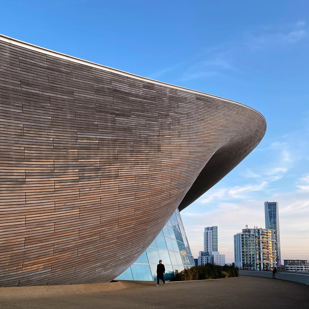 Exterior of a curved wooden building with skyscrapers in the background
